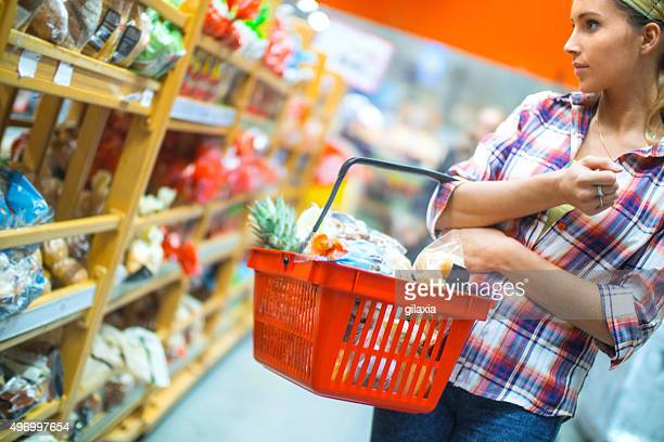 woman buying food in supermarket. - convenience store stock photos and pictures