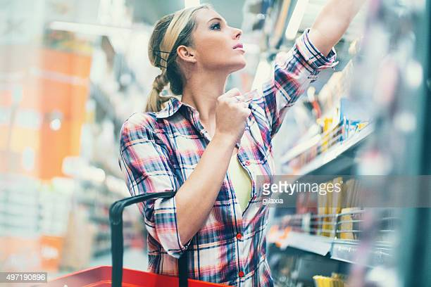 woman buying food in supermarket. - convenience stock photos and pictures