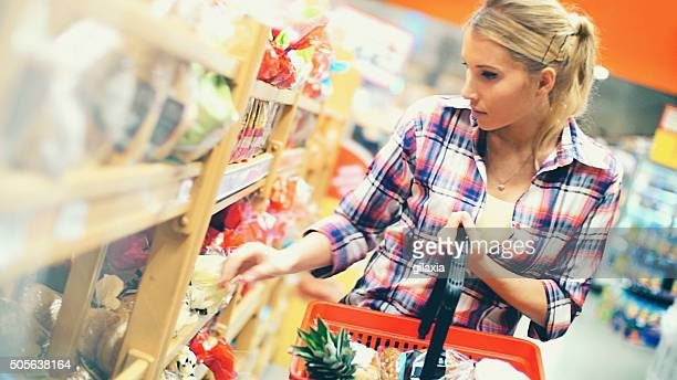 woman buying food in supermarket. - basket stock photos and pictures