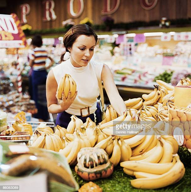 Woman buying fresh bananas at grocery store