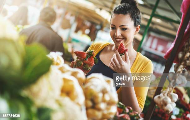 Woman buying fresh fruits and vegetables.