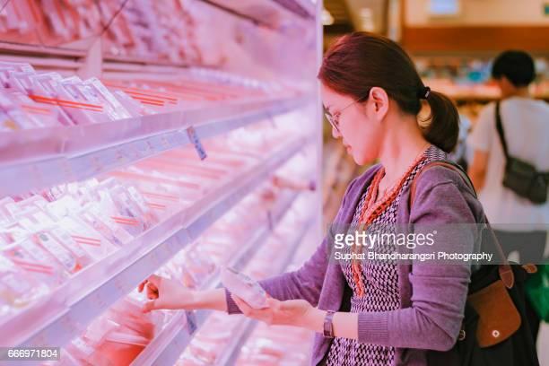 Woman buying fresh meat at supermarket