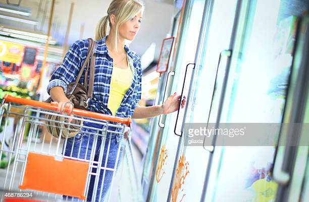 Woman buying frozen food in supermarket.
