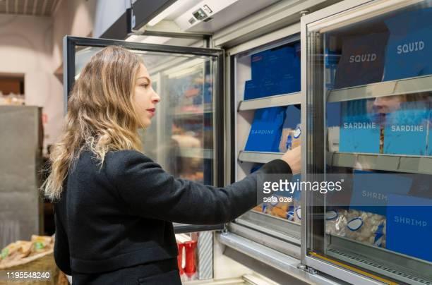 femme achetant la nourriture congelée des fruits de mer au supermarché - aliment surgelé photos et images de collection