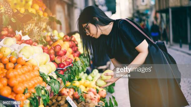 woman buying fruits on street market - apple fruit stock photos and pictures