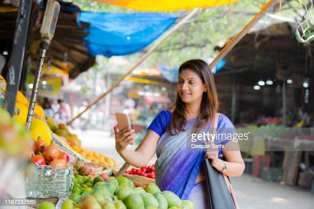 woman buying fruits on street market stock photo - apple pay mobile payment stock pictures, royalty-free photos & images