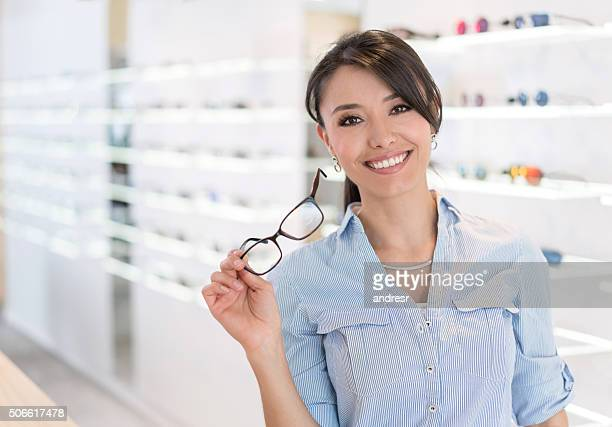 Woman buying glasses at the optician'€™s shop