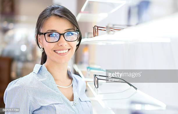 woman buying glasses at the optician's shop - optometry stock pictures, royalty-free photos & images