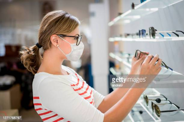 woman buying glasses at the optics during the pandemic and wearing a facemask - optical instrument stock pictures, royalty-free photos & images