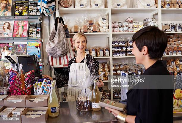 Woman buying goods at deli shop