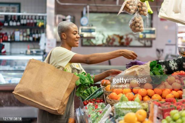 woman buying groceries in a market hall - bag stock pictures, royalty-free photos & images