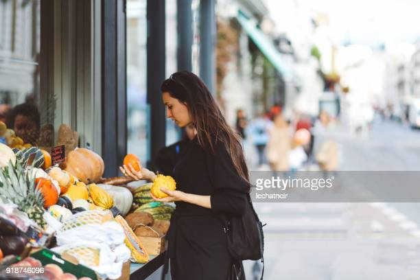 woman buying groceries in london street market shop - east london stock pictures, royalty-free photos & images