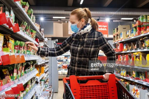 woman buying grocery in supermarket during covid-19 pandemic - avoidance stock pictures, royalty-free photos & images