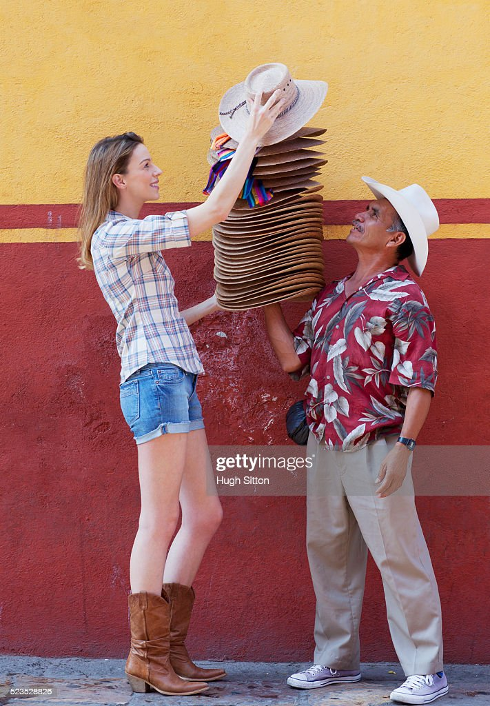 Woman buying hats from street vendor : Stock Photo