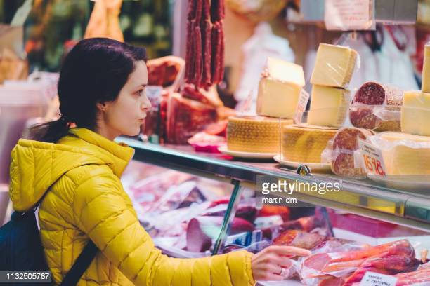 woman buying healthy food at the farmer's market - butcher's shop stock pictures, royalty-free photos & images