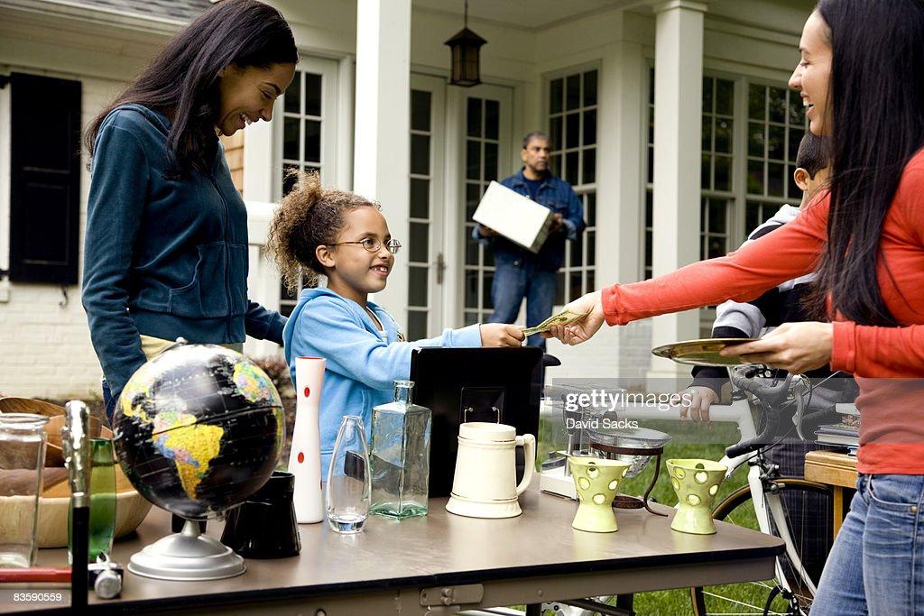 Woman buying item at yard sale : Stock Photo
