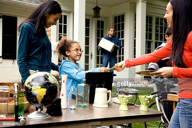 Woman buying item at yard sale