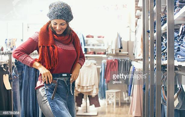 woman buying jeans at retail store. - trousers stock pictures, royalty-free photos & images
