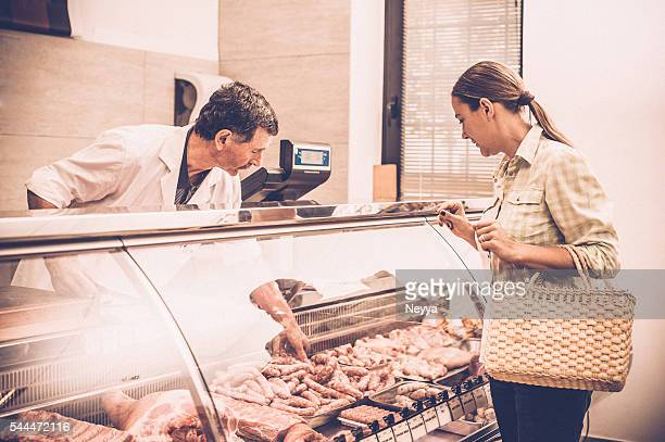 woman buying meat at the butcher shop