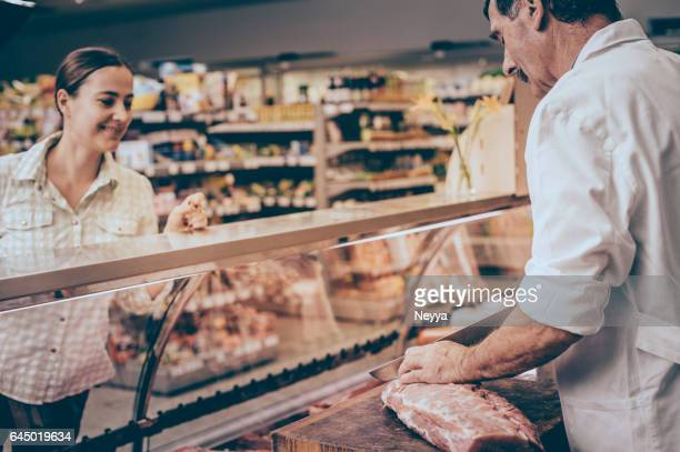woman buying meat at the butcher shop - delicatessen stock photos and pictures