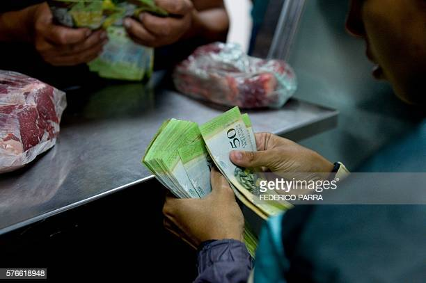 A woman buying meat counts her money in a supermarket at the Petare neighborhood in Caracas on July 16 2016 The Venezuelan military began overseeing...