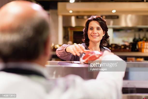 woman buying meat from butcher - klanten georiënteerd stockfoto's en -beelden