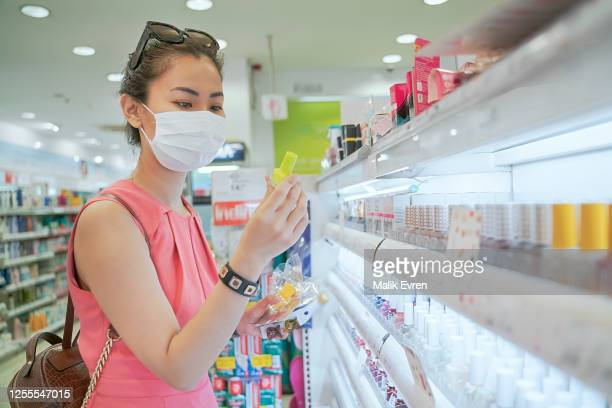 woman buying nail polish beauty product during pandemic with face mask - face mask beauty product stock pictures, royalty-free photos & images