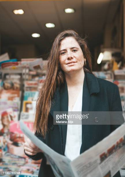 woman buying newspaper - news stand stock pictures, royalty-free photos & images