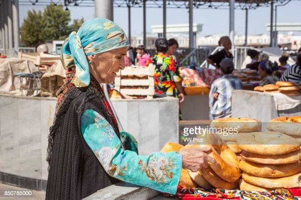 Woman buying non bread Siyob Market also known as Siab Market Samarkand Uzbekistan