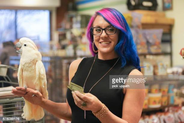 woman buying parrot in pet store - blue hair stock pictures, royalty-free photos & images