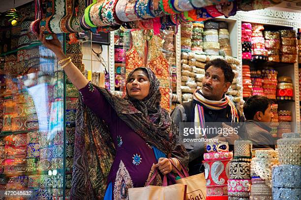 Woman buying ribbon in Old Delhi, India
