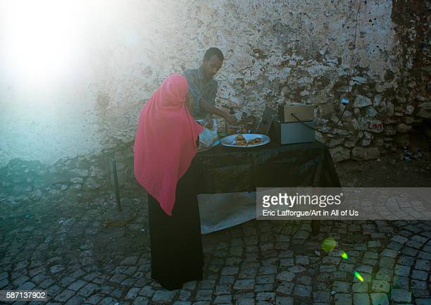 Woman buying samosas in the street harari region harar Ethiopia on March 4 2016 in Harar Ethiopia