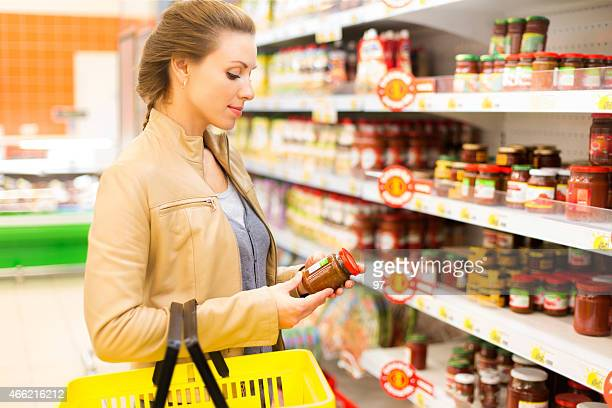 Woman buying sauce in supermarket