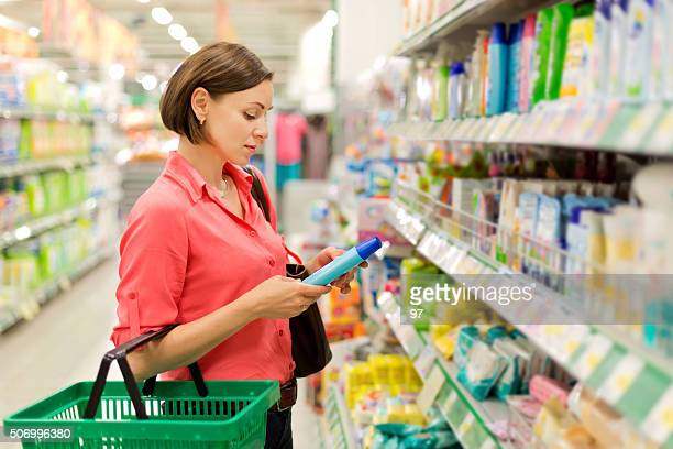 woman buying shampoo - shampoo stockfoto's en -beelden