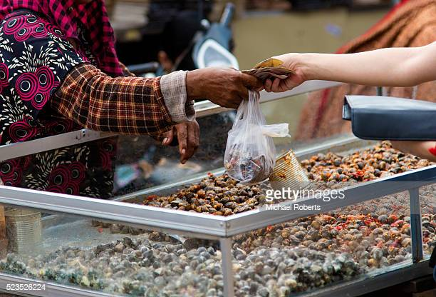 Woman buying shellfish from a street vendor at a food market in Cambodia