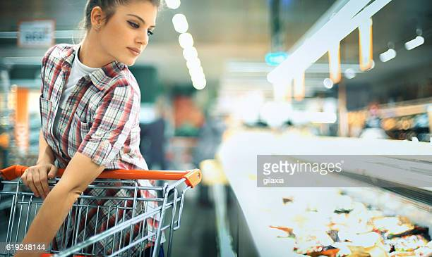 Woman buying some frozen food at local supermarket.