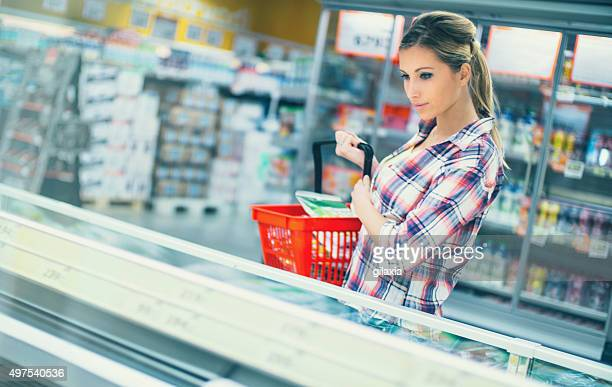 Woman buying some frozen food in supermarket.