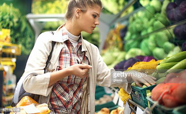 woman buying some fruit in supermarket. - produce aisle stock photos and pictures