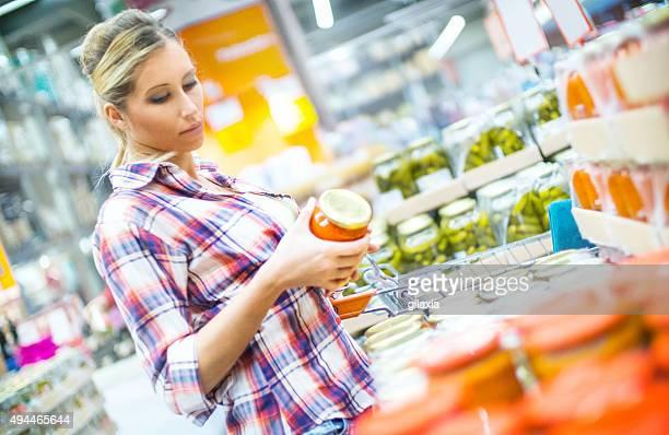 Frau Kauf einige eingelegtem Gemüse im Supermarkt.