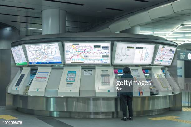 Woman Buying Train Ticket at Automatic Ticket Machines in Tokyo Train Station