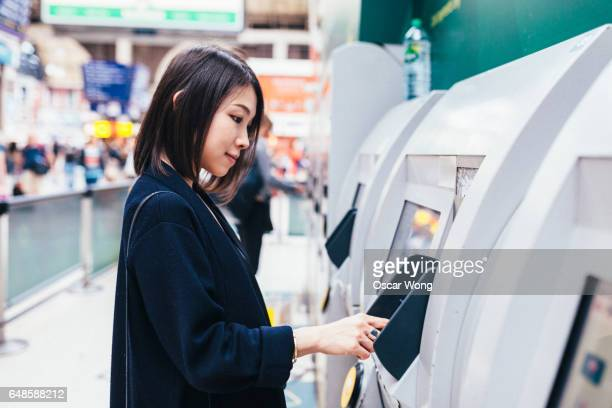 Woman buying train ticket in station