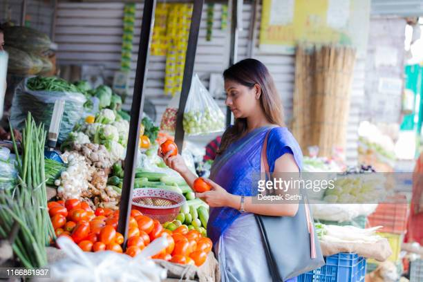 woman buying vegetables at a street vendor. stock photo - vendor stock pictures, royalty-free photos & images