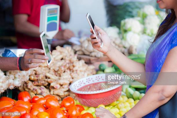 woman buying vegetables at a street vendor. stock photo - market vendor stock pictures, royalty-free photos & images