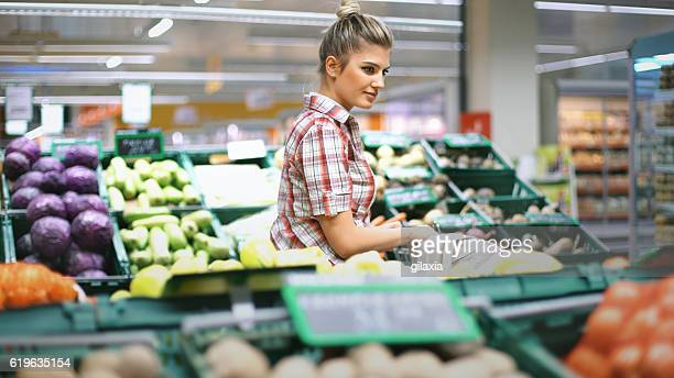 woman buying vegetables at a supermarket. - produce aisle stock photos and pictures