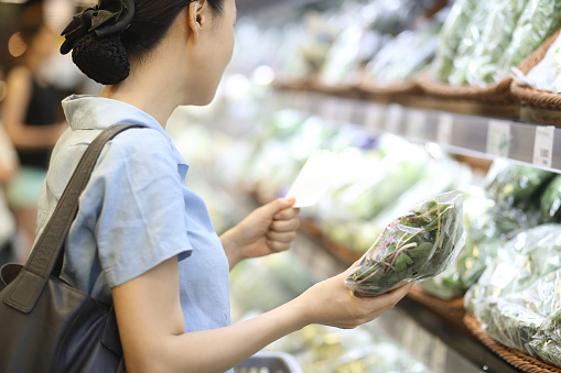 Woman buying vegetables at a supermarket. - gettyimageskorea