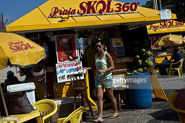 A woman buys a beer at a Cia de Bebidas das Americas Skol brand beer stand at Copacabana beach on Saturday Aug 4 2013 Investors are betting on...