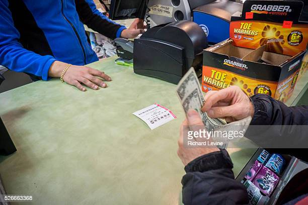 A woman buys a chance to win the $15 billion Powerball jackpot on Wednesday January 13 2016 The jackpot has rolled over 18 times with no winner with...