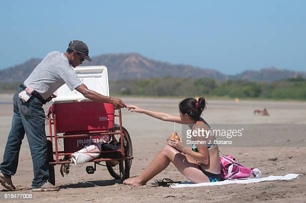 Woman buys a cocnut on the beach at Playa Tamarindo in Costa Rica.
