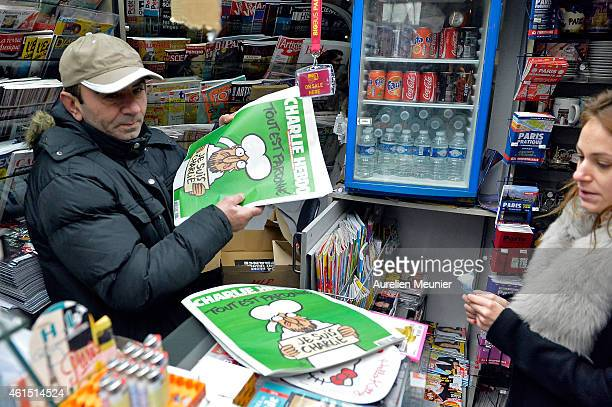 Woman buys a copy of the new edition of Charlie Hebdo magazine at a Pigalle newsstand on January 14, 2014 in Paris, France. Three million copies of...