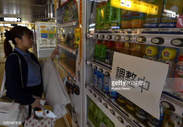 A woman buys a drink at JR Sapporo Station on Sept 12 from a vending machine whose lights are turned off to save electricity amid continuing power...